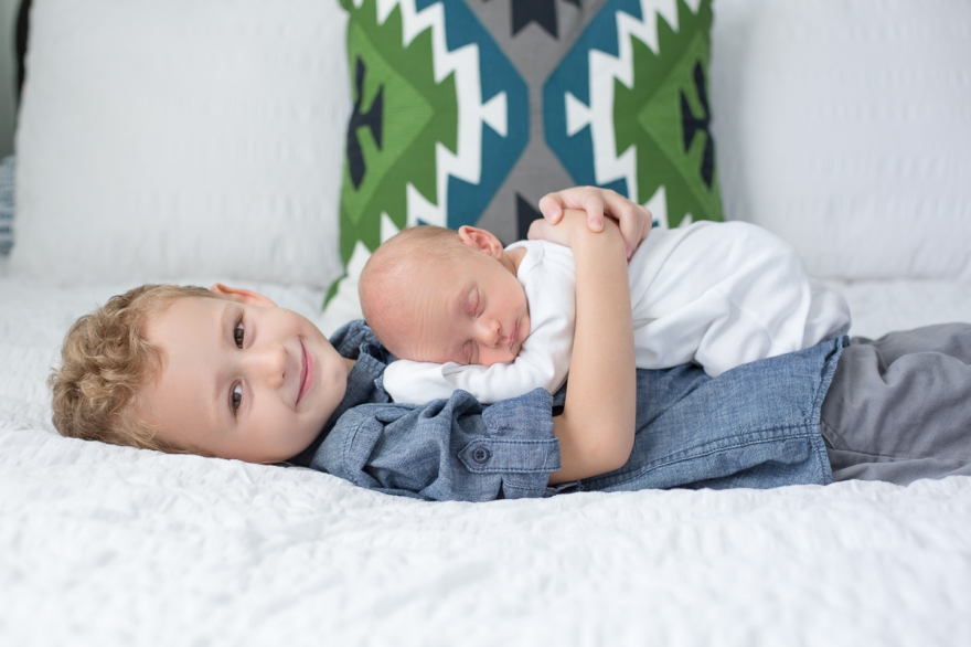 west palm beach lifestyle newborn photography, in home session, blues and greens, big brother snuggling baby